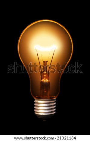 Classical old style bulb shining on black background.