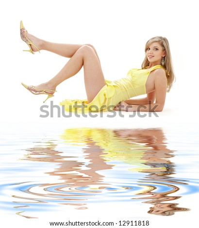classical pin-up image of pretty lady in yellow dress on white sand - stock photo