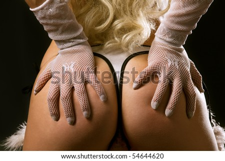 Classical pin-up image of sexy woman bum on dark background - stock photo