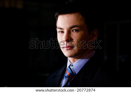 Classical portrait of young businessman over dark background
