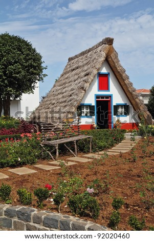 Classical small house  on Madiera. A bright red door, a straw triangular roof, a small front garden and an accurate stone path - stock photo