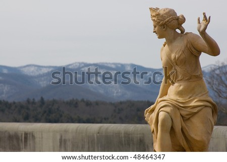 Classical statue overlooking mountains - stock photo