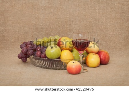 Classical still-life with fruit and a glass against a canvas - stock photo