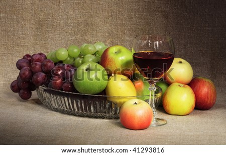 Classical still-life with fruit and a glass of red wine against a canvas - stock photo