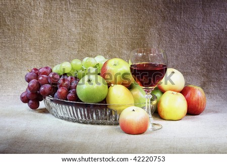 Classical still-life with fruit and a wineglass against a canvas - stock photo