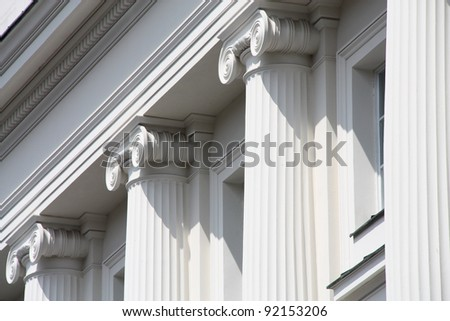 Classical style columns in ionic order on exterior of modern windowed building.