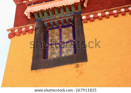 Classical tibetan window under canopy on a red and yellow painted wall of building in the Gelugpa-Yellow Hat buddhist order Sera-Wild Roses gonpa-monastery. Lhasa pref.-Tibet A.R.-China. - stock photo