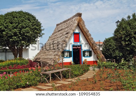Classical triangular small house of the first settlers on island Madiera. A bright red door, a straw triangular roof, a small front garden and an accurate stone path - stock photo