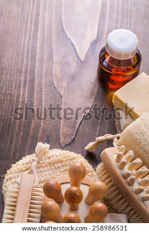 classical wooden massagers wisp brushes loofah soap and oil on vintage wooden board with copyspace  - stock photo