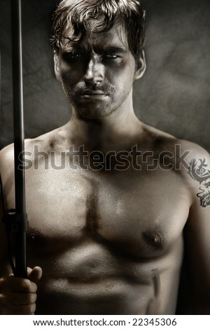 Classically stylized portrait of a shirtless young man portraying tribal warrior holding spear - stock photo