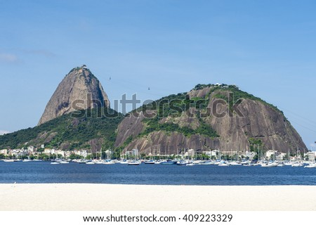 Classid daytime scenic profile view of Pao de Acucar Sugarloaf Mountain in Rio de Janeiro, Brazil standing above Botafogo Bay - stock photo