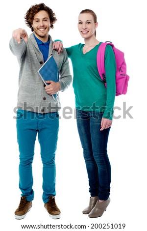 Classmates posing together, pointing towards camera - stock photo
