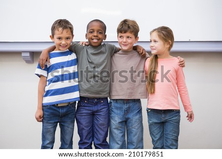 Classmates smiling at camera in classroom at the elementary school - stock photo