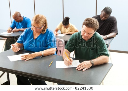 Classrom of adult education students taking a test in school .  Focus on the guy in the front. - stock photo