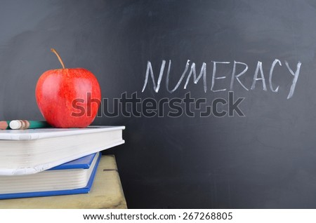Classroom,apple,books and blackboard with handwriting in white chalk - stock photo