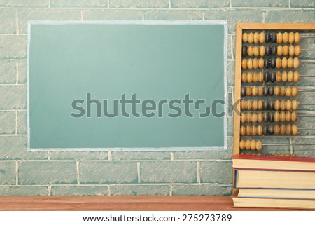 Classroom, books and abacus about blackboard with copy space - stock photo