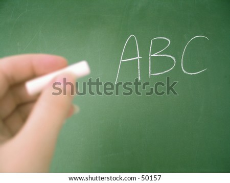 Classroom chalkboard .. hand with chalk. Focus on chalkboard. - stock photo