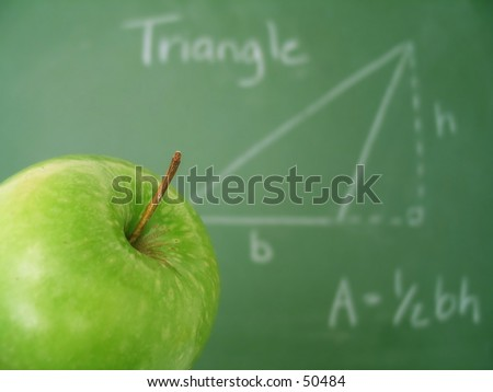 Classroom chalkboard with math, apple in focus. - stock photo