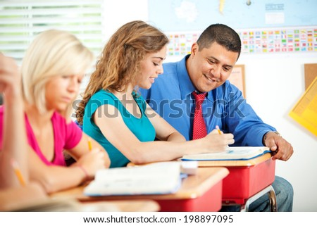 Classroom: Hispanic Teacher Helps Female Student With Assignment - stock photo