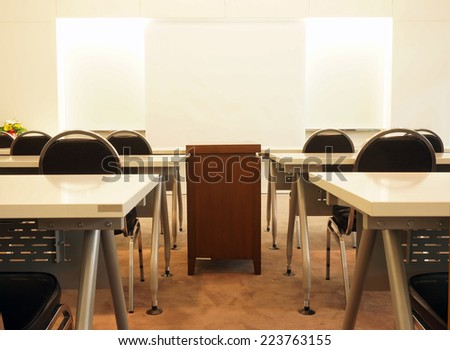 Classroom or meeting on campus, include tables, chairs and projection screen for slide presentation.