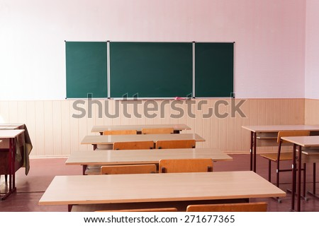 Classroom with empty wooden desks and with green board , in scool