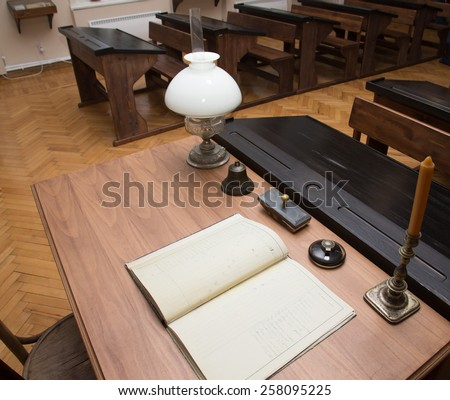 Classroom with parquet floor and rows of old desks. Table of teacher with journal, lamp, bell and candle. - stock photo