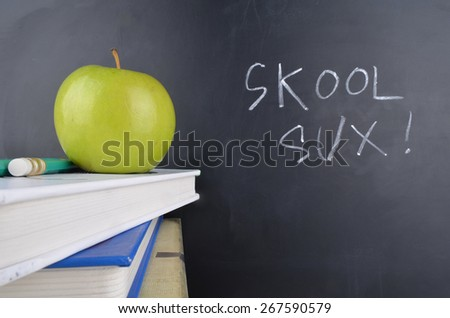 Classroom with red apple,books and handwriting in white chalk on blackboard