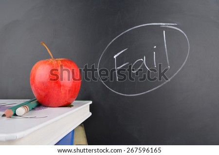 Classroom with red apple,books and handwriting in white chalk on blackboard saying fail - stock photo