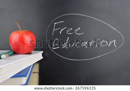 Classroom with red apple,books and handwriting in white chalk on blackboard saying free education - stock photo