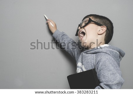 classroom, young student writing on a blackboard school with a book in hand and big glasses - stock photo