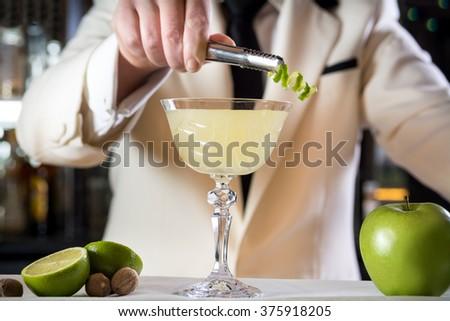 Classy bartender barman decorating rum based drink cocktail lime zest shaker in bar uniform cruise ship  - stock photo