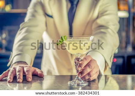 Classy bartender barman serves plain classic rum based drink cocktail lime decoration shaker in bar uniform cruise ship Instagram style filter