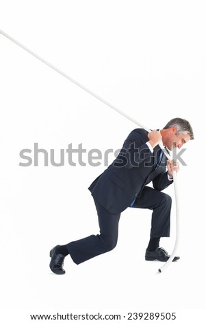 Classy businessman pulling a rope on white background - stock photo