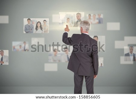 Classy businessman selecting futuristic interface showing coworkers - stock photo