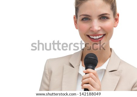 Classy businesswoman holding microphone on white background - stock photo
