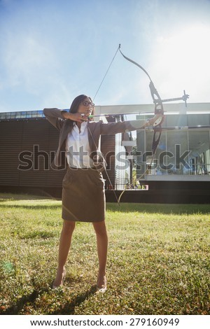 Classy Businesswoman Practicing Archery In Front Of Business Building - stock photo