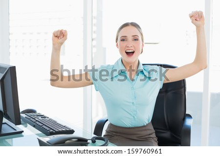 Classy cheerful businesswoman cheering with raised arms in bright office - stock photo