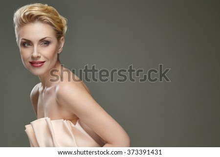 Classy chic. Horizontal portrait of a stunning blonde woman posing in studio looking away smiling copyspace on the side - stock photo