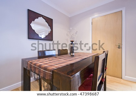 Classy dining area with a dining table and chairs made of massive wood - stock photo