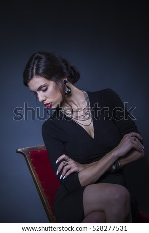 Classy elegant young woman in black sitting on a red chair