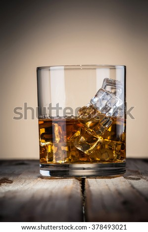 Classy glass of whiskey with ice on wooden table - stock photo