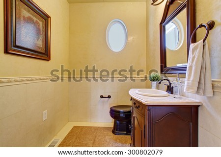 Classy half bathroom with small oval window, and beige tile floor. - stock photo