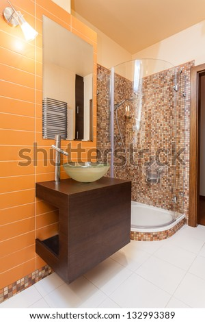 Classy house - bathroom with orange wall and wooden counter