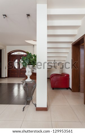 Classy house - stairs, armchair and a pillar - stock photo