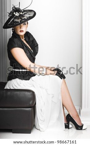 Classy lady in elegant haute couture ensemble with a fascinator hat and accessories sitting demurely on a seat with erect posture - stock photo