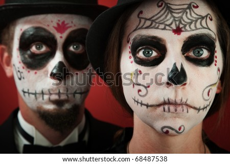 Classy middle-aged couple pose in All Souls Day Makeup - stock photo