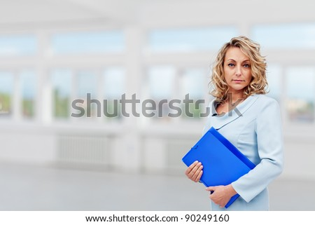 Classy real estate agent in large room with blue portfolio - copy space - stock photo