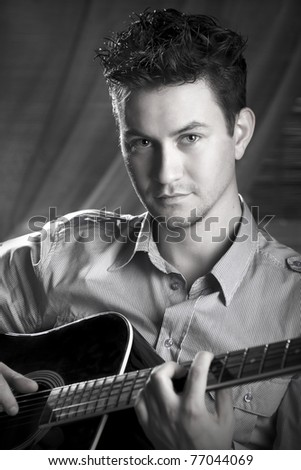 Classy romantic guy sitting on a chair with a guitar in his hands. Black and white photography. - stock photo