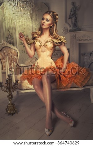 classy woman in corsetry sitting on an ottoman - stock photo