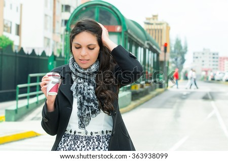 Classy woman wearing dark coat and black white clothing urban environment holding coffe mug, posing with disappointed facial expression in front of bus station